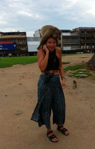 Aap in Lopburi klimt op schouder